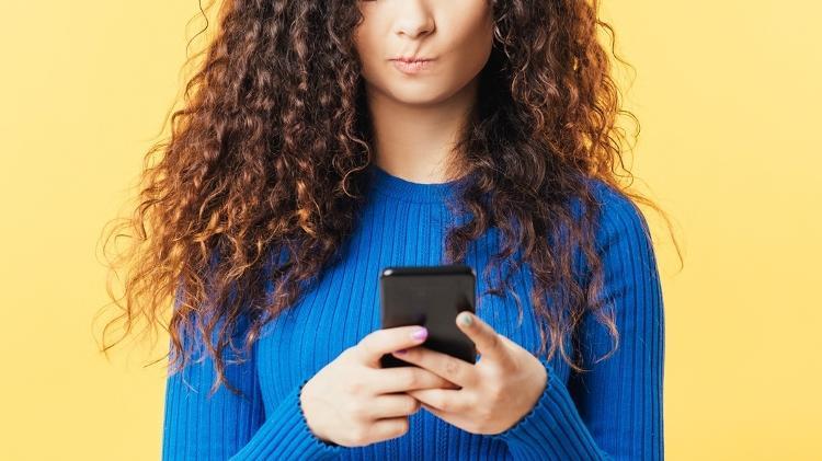 Mulher olhando para celular, falando sobre o impacto que afeta o vírus, rede social - golubovy / Getty Images / iStockphoto - golubovy / Getty Images / iStockphoto